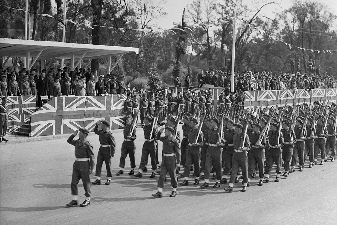 Premierminister Churchill (auf der Tribüne in der ersten Reihe mittig stehend) salutiert der Ehrenformation britischer Truppen, die bei der am 21. Juli 1945 in Berlin stattfindenden Siegesparade vorbeimarschieren werden.