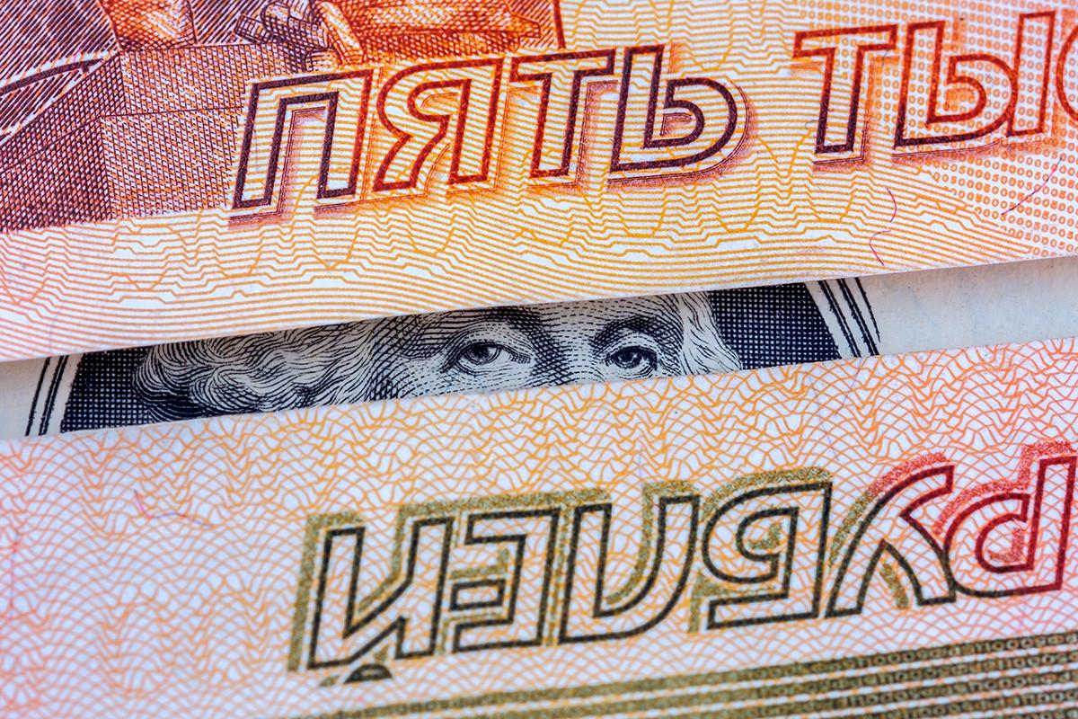 George Wshington kuka z dolarskega bankovca med dvema bankovcema za pet tisoč rubljev.