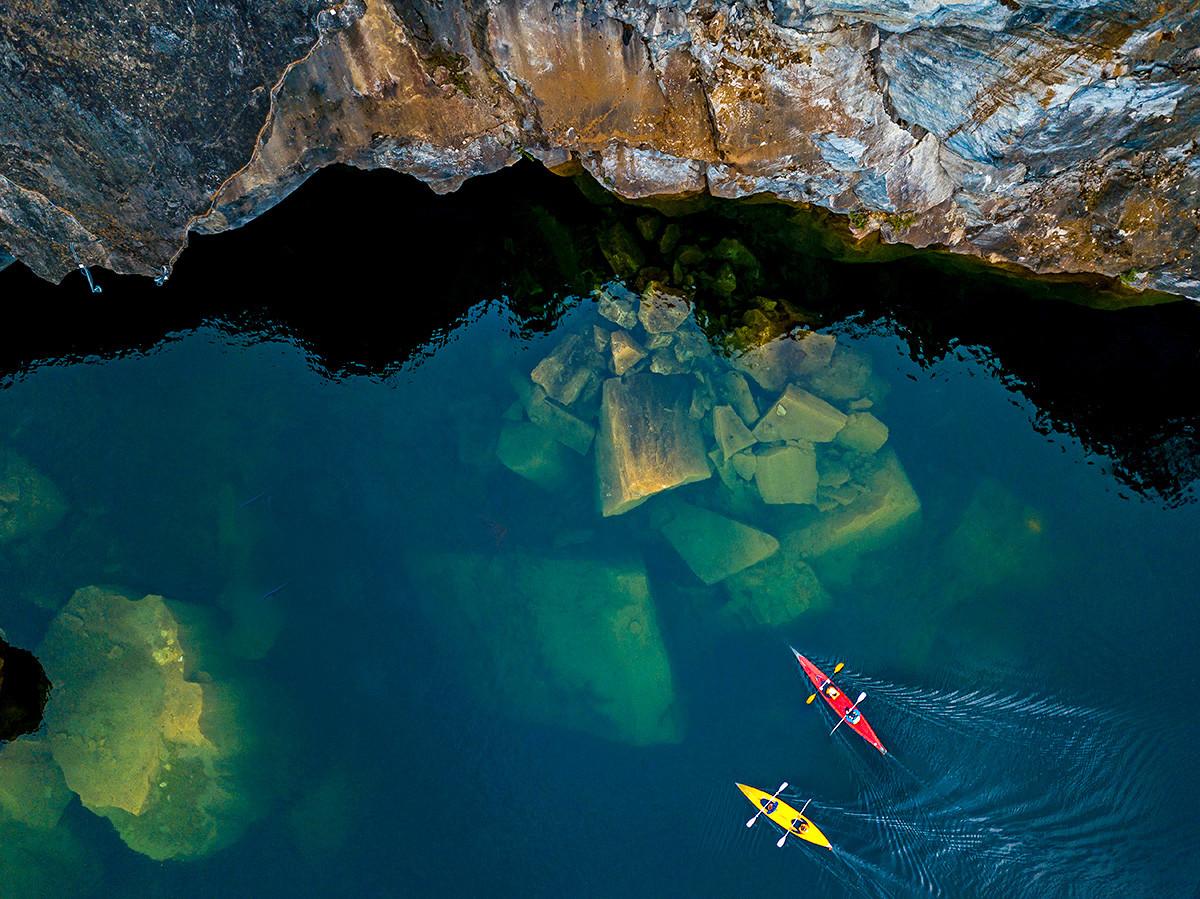 Kayakers sailing over sunken boulders in Lake Light.