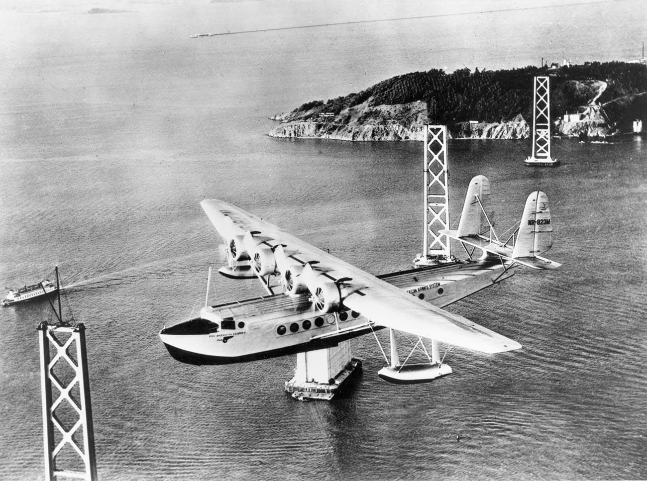 """Sikorsky S-42 """"Pan American Clipper"""" прелеће залив Сан Франциска на путу за Хаваје. Види се конструкција моста Сан Франциско – Окланд у изградњи. Око 1934."""