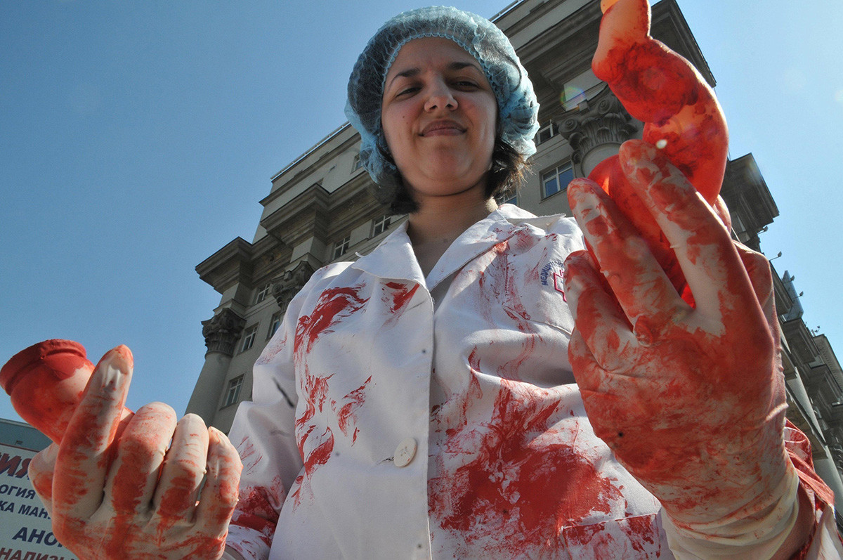 Demonstracija splava v osrednji Moskvi. Udeleženci shoda držijo okončine lutke, prekrite z rdečo barvo