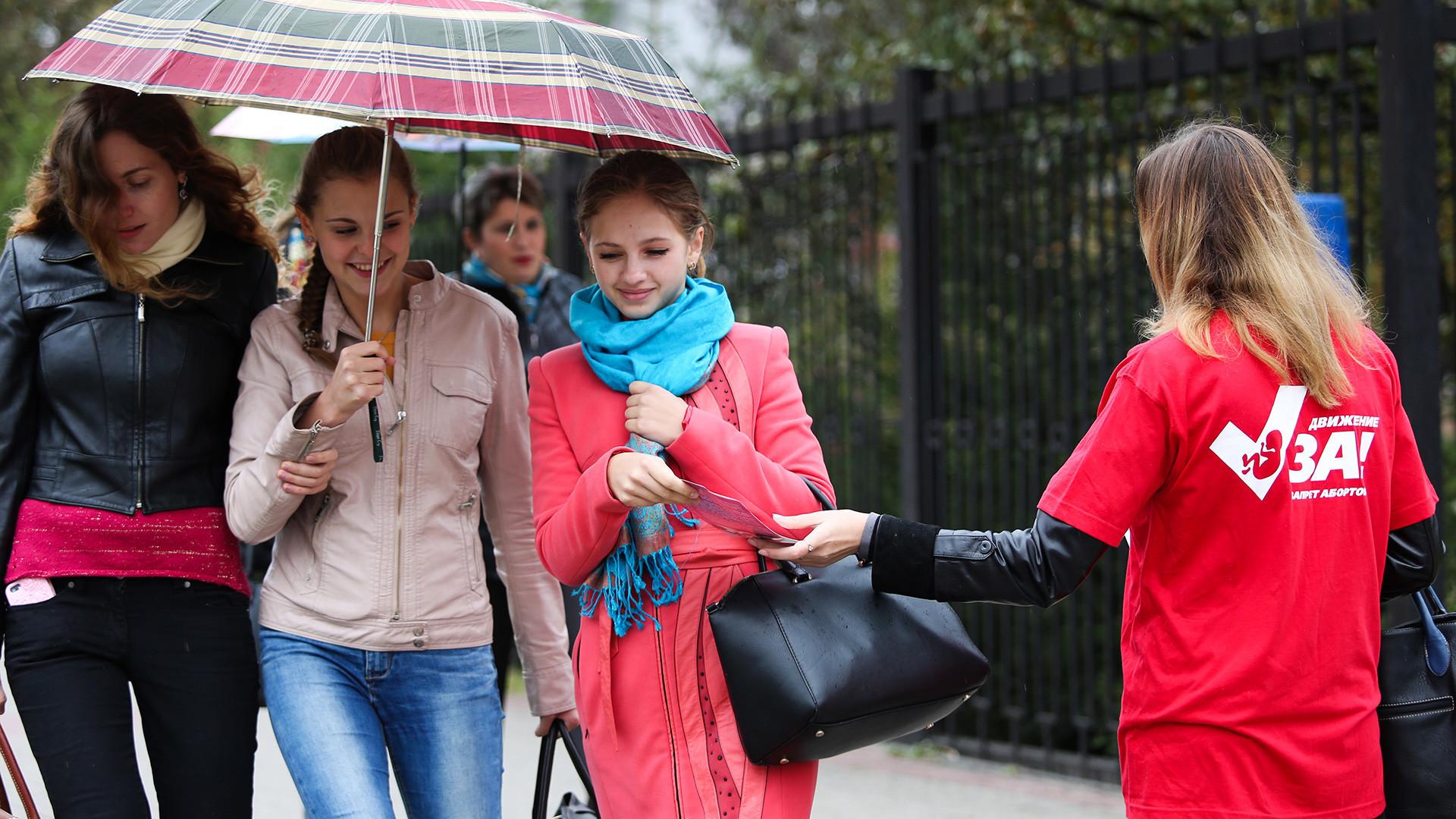 Aktivistka proti splavu razdeljuje letake pred prednatalnim centrom v mestu Belgorod