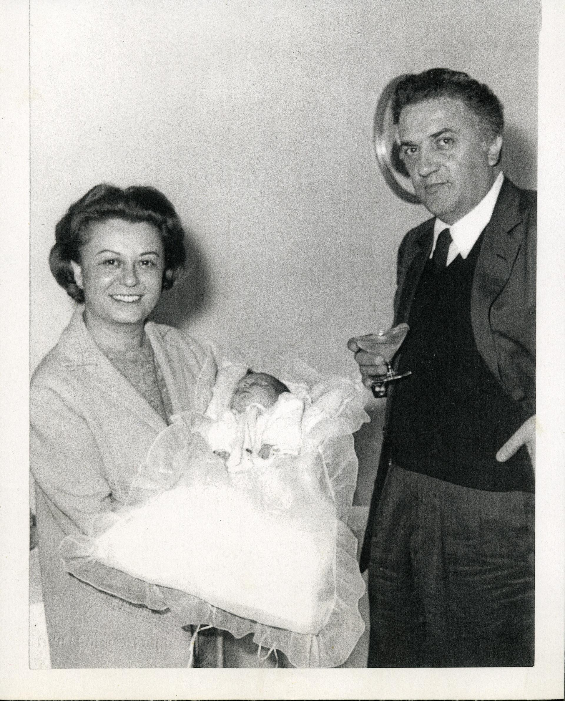 Federico Fellini con Giulietta Masina, che tiene in braccio la nipote del regista, Francesca, nel giorno del suo Battesimo
