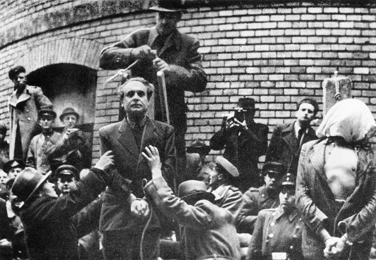 Унгарският нацистки лидер Ференц Салаши стои до екзекутиран човек със завързани ръце, чувал на главата и разкопчана риза, докато мъж зад Салаши подготвя примката за публичното му обесване, Унгария, 1946 г.