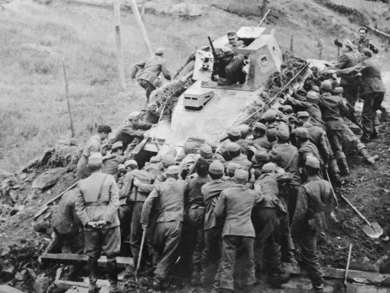 Over 50 Hungarian soldiers are putting their shoulders to the tractor wheels in an effort to recover this disabled Soviet tank.