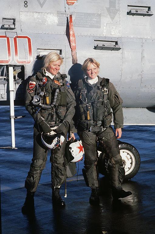 """Las tenientes de la Marina de los EE UU.  Lori """"Wrench"""" Melling (izquierda) y Laura """"Moose"""" Mason, Escuadrón 34 de Guerra Electrónica Táctica (VAQ-34), delante de su avión EA-7L en 1987. Pueden apreciarse las estrellas rojas de la Fuerza Aérea soviética en sus cascos."""