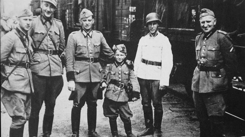 Алекс Курзем (трети оддесно) со пушка на рамото, во друштво на нацистички СС-офицери за време на Втората светска војна.