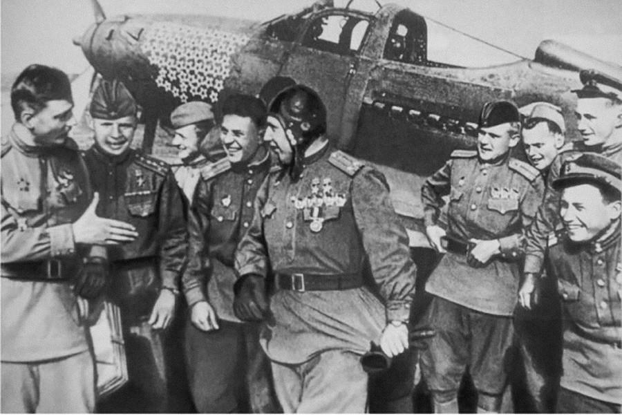 アレクサンドル・ポクルィシキン(ヘルメットをかぶる方)を祝う同僚たち、第16戦闘機航空連隊、1944年の夏。