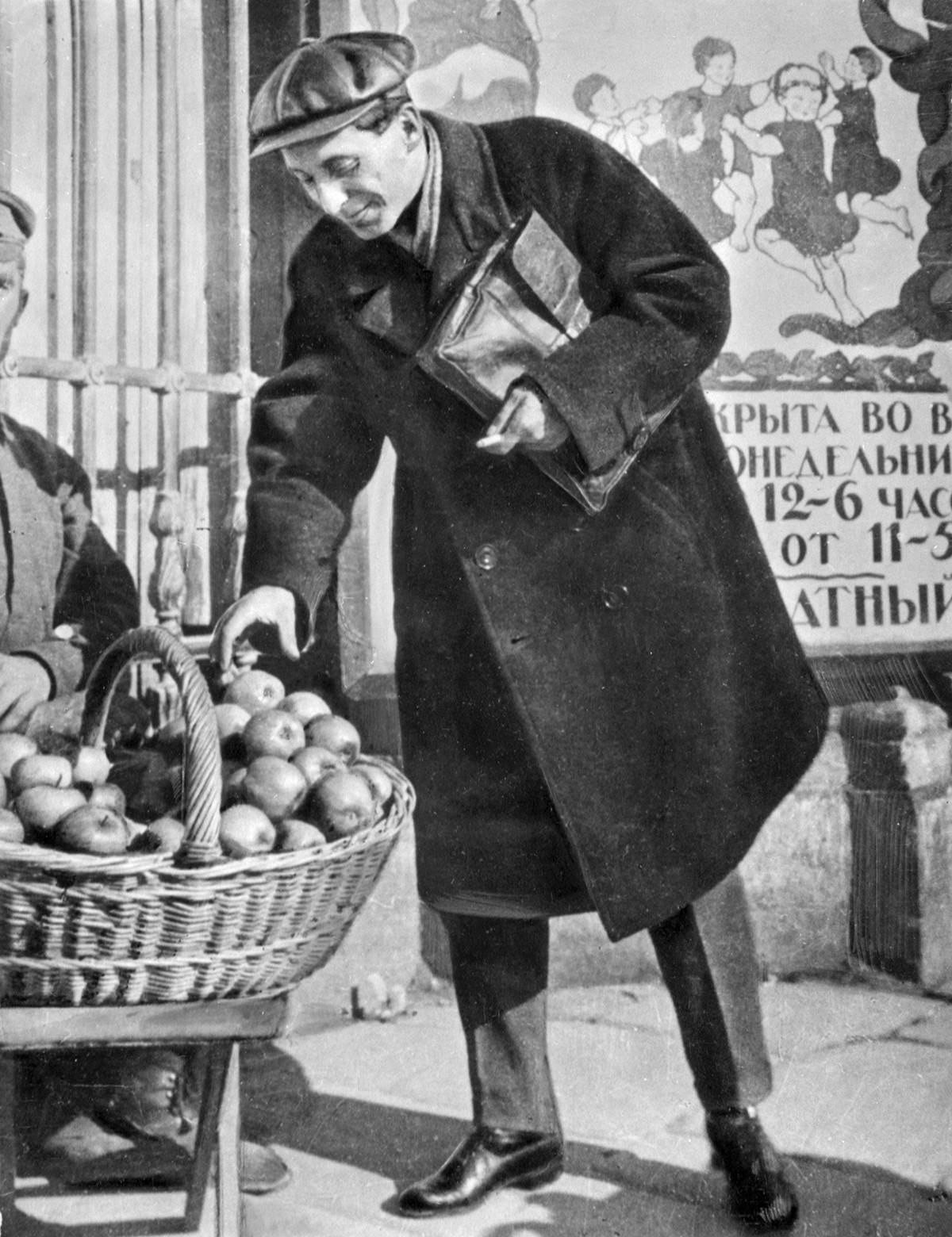 リンゴを買っている作家ミハイル・ゾシチェンコ