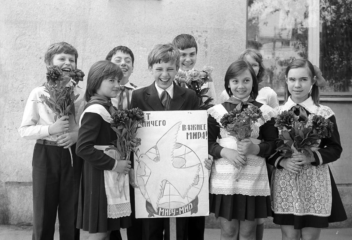 Skupina otrok, ki drži plakat, na katerem piše: