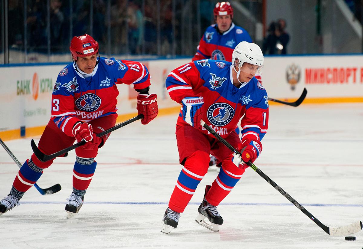 Presiden Rusia Vladimir Putin (kanan) dan kurator konferensi Volgaskaya Oblast Valery Kamensky dalam pertandingan antara tim nasional 'Zvezdy' Liga Hoki Malam (NHL) dan tim nasional Dewan dan tamu kehormatan NHL.
