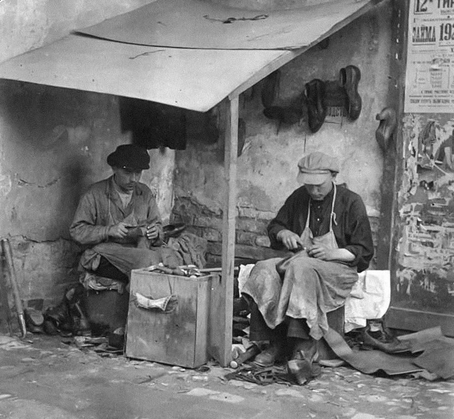 Ces cordonniers travaillant dans la rue avec des matériaux et des outils simplifiés étaient appelés « cordonniers froids ». Cette expression s'appliquait aussi aux personnes qui n'étaient pas très douées pour le travail. Photo de Kimry, dans la région de Tver, années 1920.