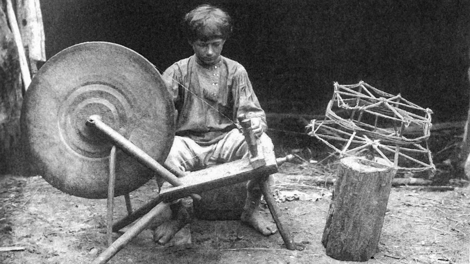 Un garçon enroule des fils pour la fabrication de bandes de calicot. Gouvernorat de Riazan, village de Alekseïev, 1913.