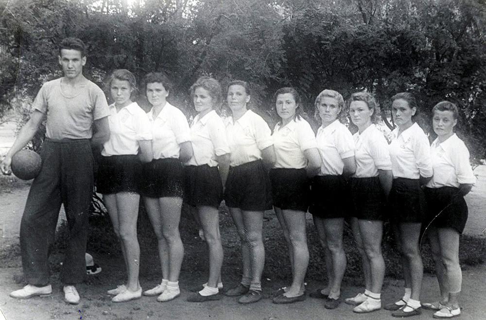 Técnico de time feminino de vôlei com alunas na cidade russa de Kurgan, 1952