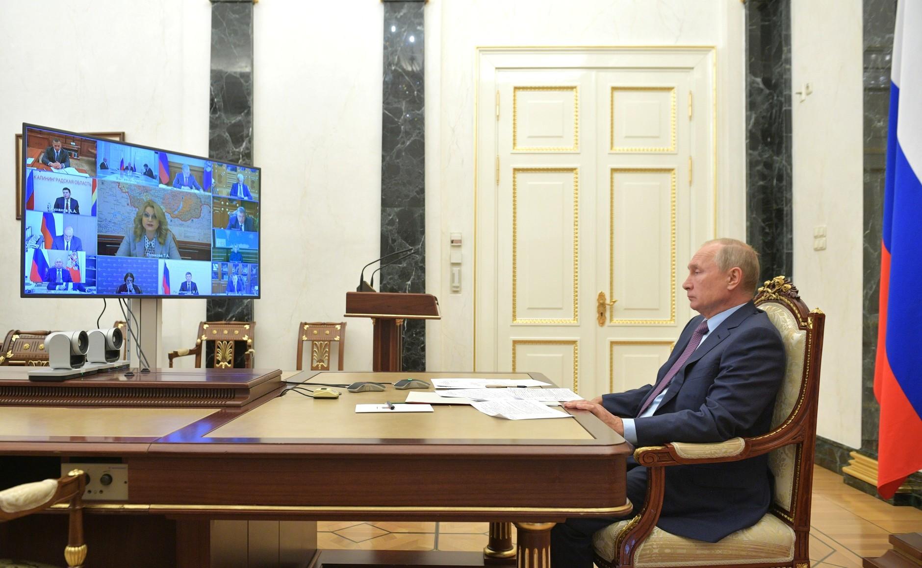 Presiden Rusia Vladimir Putin mendengarkan pemaparan Menurut Wakil Perdana Menteri Rusia Tatyana Golikova (pada layar utama), dalam rapat kabinet virtual, Moksow, Kamis (15/10).