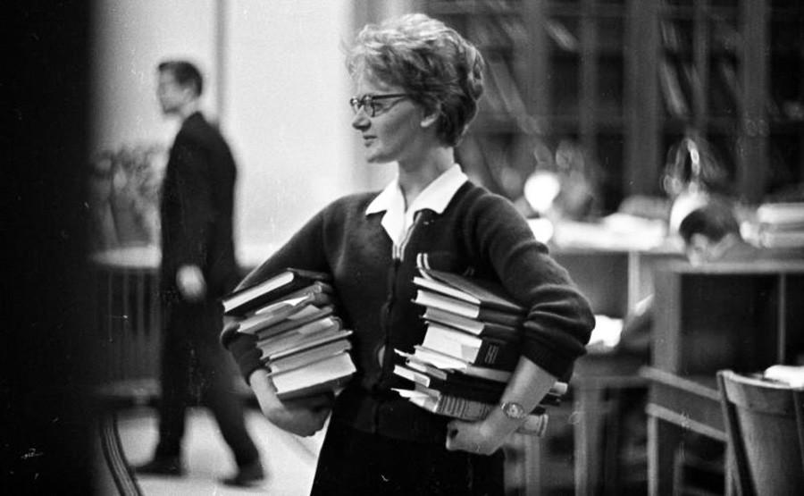 Seorang mahasiswi tengah membawa banyak buku, 1963 – 1964.