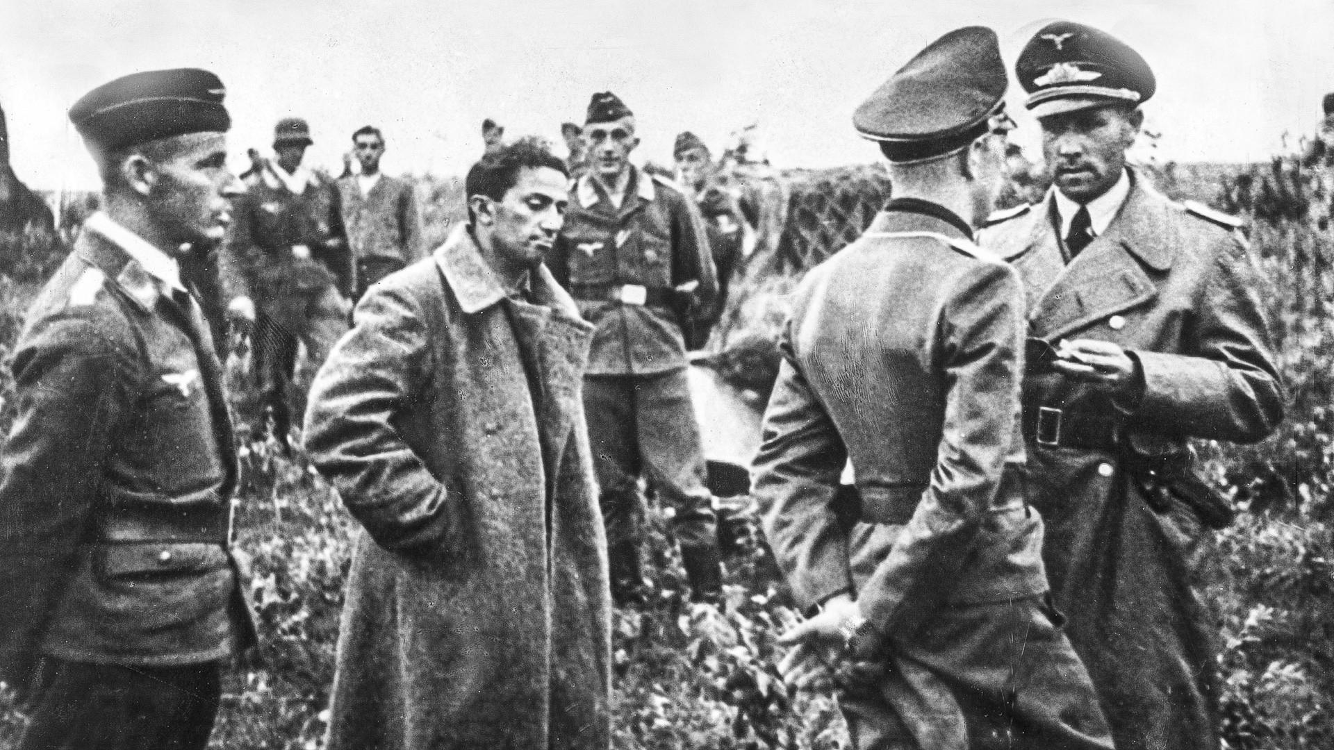 Iakov Djougachvili entouré d'officiers allemands après sa capture. En attente d'un transfert aérien vers l'arrière pour être interrogé.