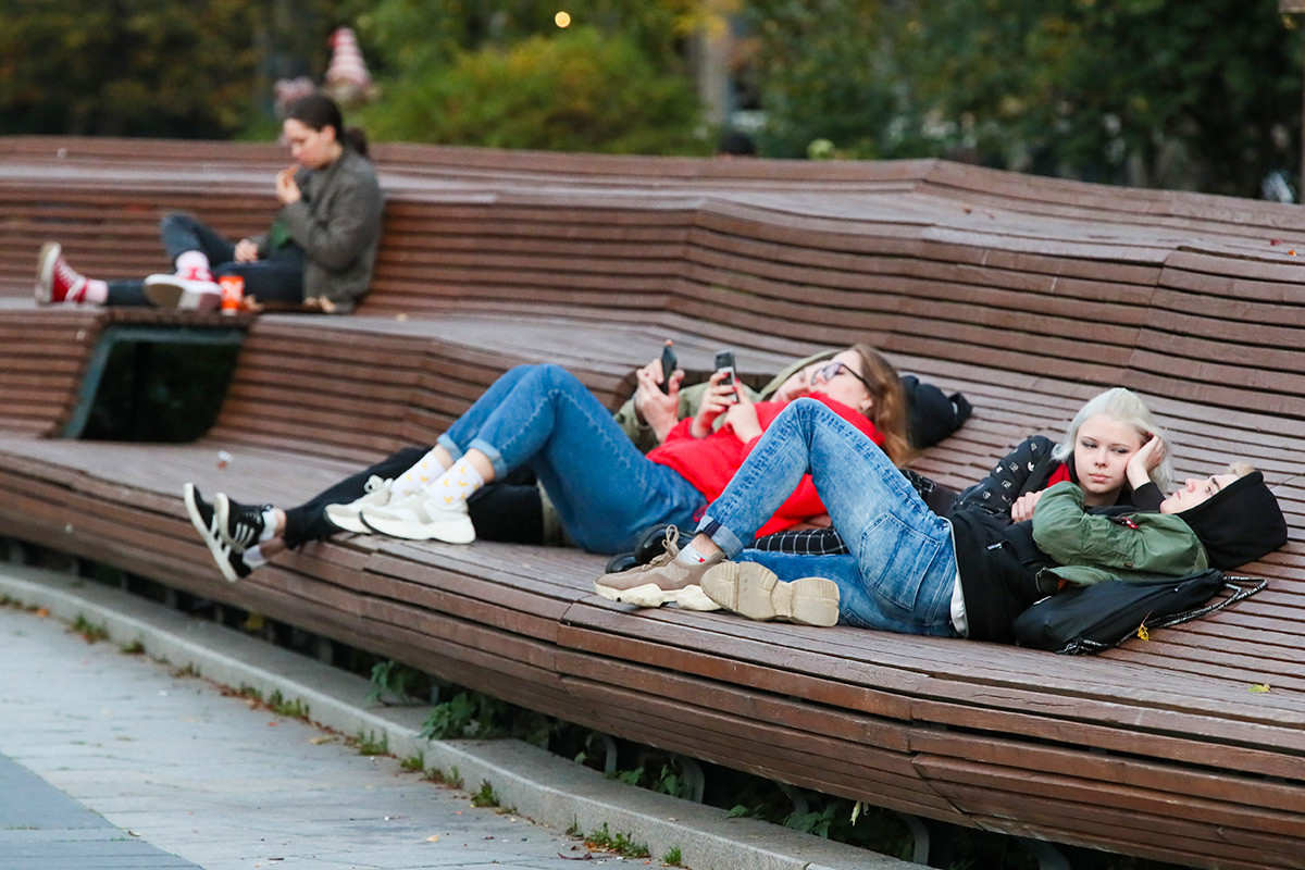 Moscow, Russia - October 11, 2020: People lie on a bench in Moscow's Muzeon Park of Arts. 4,501 new confirmed cases of the novel coronavirus infection were reported in Moscow, and 13,634 in Russia on October 11, 2020, the highest rates since the start of the pandemic