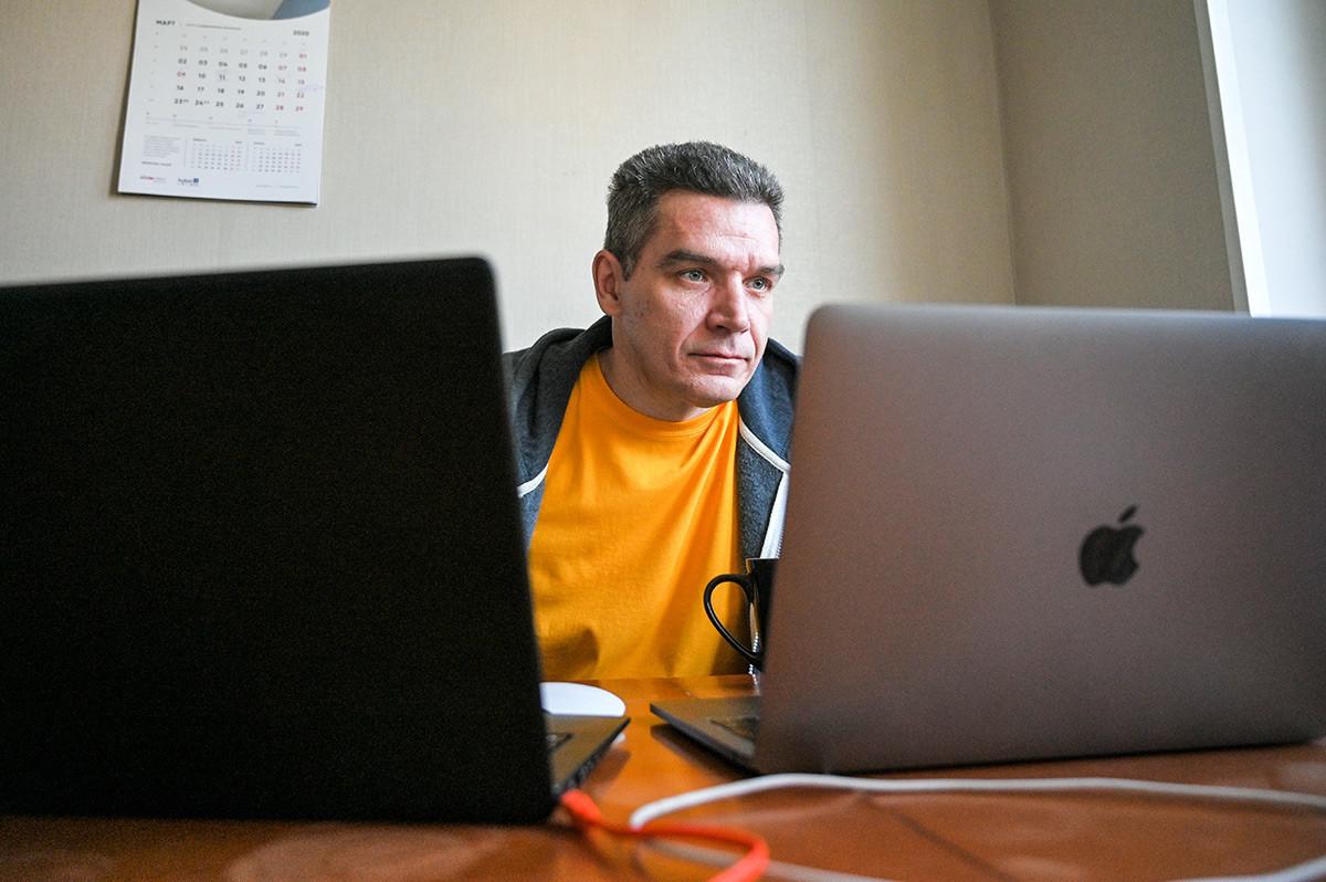 Diretor de empresa de desenvolvimento de apps móveis coordena remotamente o trabalho de seus funcionários de casa em Moscou