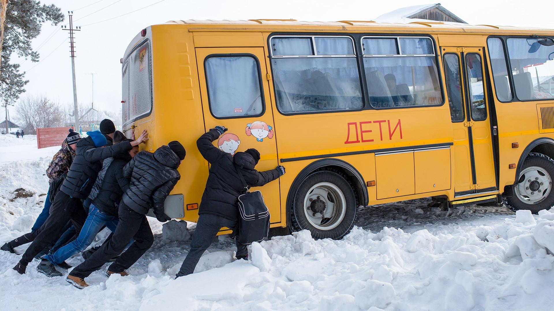 Мужчины толкают застрявший в снегу автобус во время сельской зимней спартакиады в селе Евгащино Омской области.