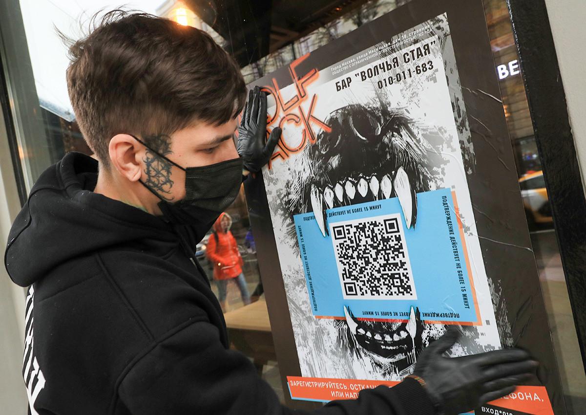 Poster dengan kode QR di pintu masuk bar, Moskow.