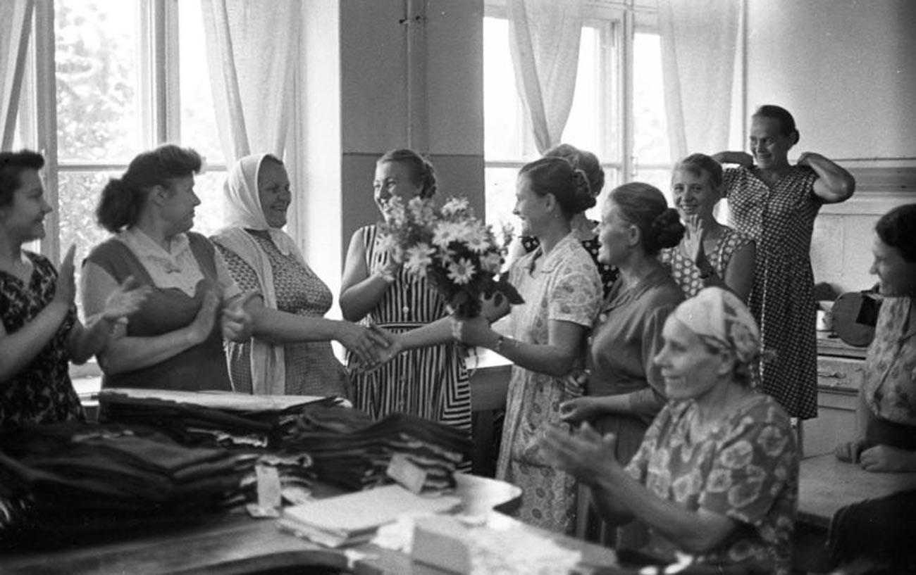 """Donne donano fiori per il compleanno di una collega nella fabbrica di abbigliamento """"40 anni del Komsomol"""" a Tiraspol, RSS Moldava, nel 1964"""