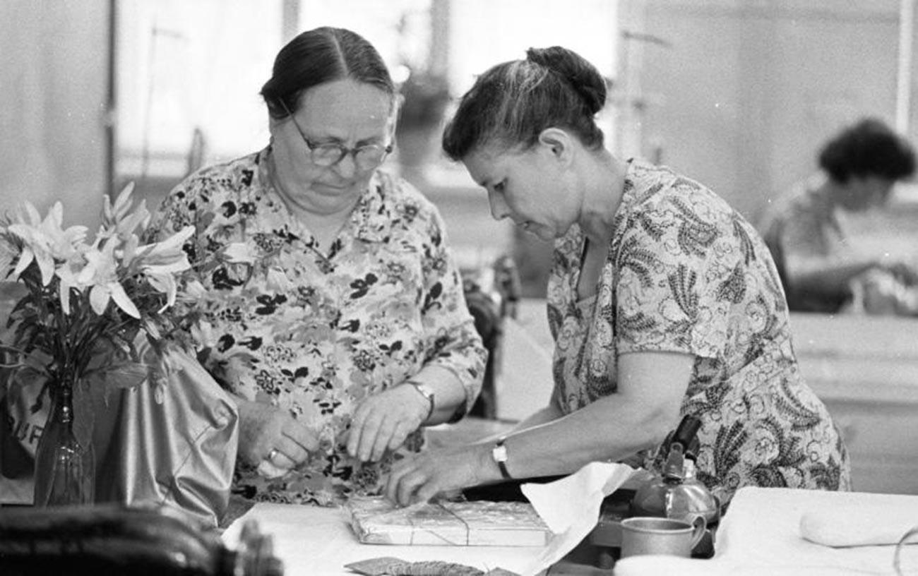 """Donne incartano il regalo per il compleanno di una collega nella fabbrica di abbigliamento """"40 anni del Komsomol"""" a Tiraspol, RSS Moldava, nel 1964"""