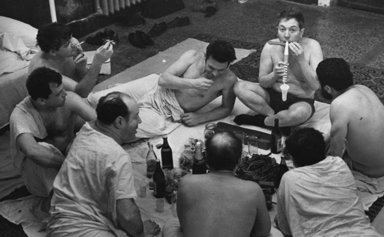 Uomini bevono birra e mangiano pesce essiccato al compleanno di Anatolij Eliseev