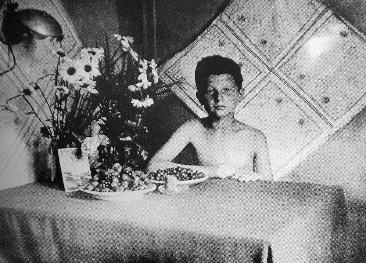 Деветгодишниот или десетгодишен Алекс Курзем седи на маса, околу 1944 година.