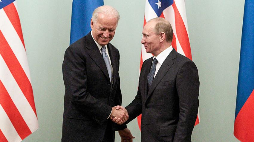 Então primeiro-ministro russo Vladimir Putin (dir.), cumprimenta o vice-presidente dos EUA, Joe Biden, durante reunião em Moscou em 10 de março de 2011