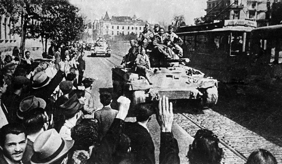 Soldados soviéticos son recibidos por los residentes de Bucarest (Rumania) cuando entran en la ciudad en estos vehículos blindados