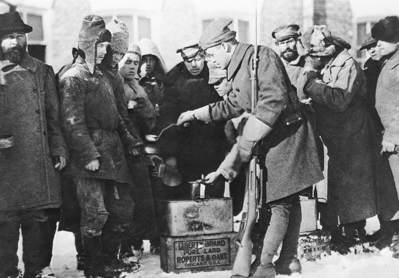 Солдат армии США раздает пищу пленным.