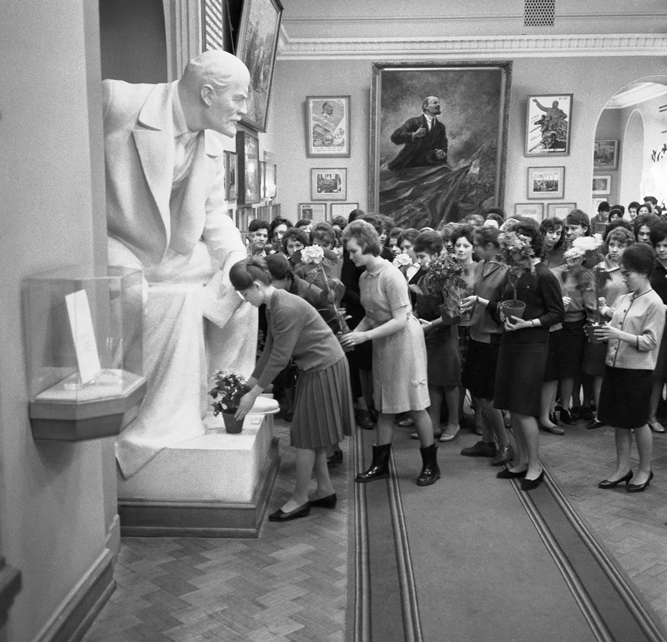 レーニン像に献花する人々