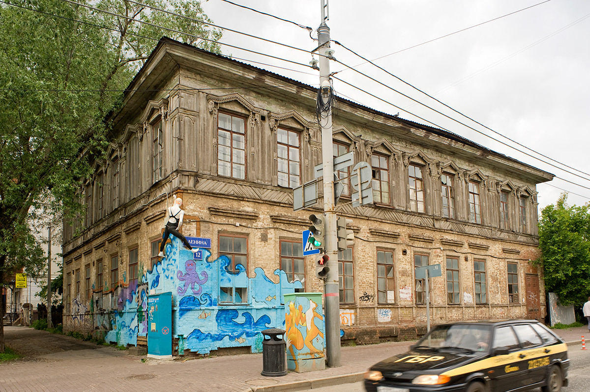 19th-century wooden house (log structure with plank siding on stuccoed brick ground story) at corner of Ostrovsky & Lenin Streets. Decorated with street art. June 15, 2014