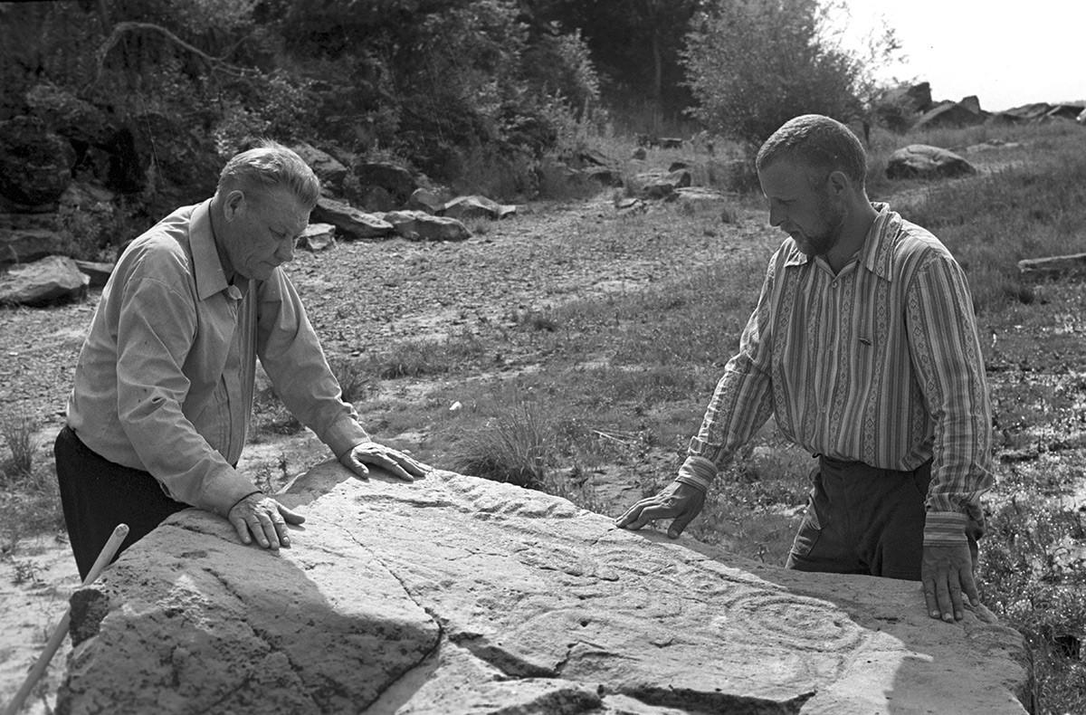 L'académicien Alexeï Okladnikov (à gauche) et le candidat en sciences historiques Alexandre Konopatski étudiant les pétroglyphes