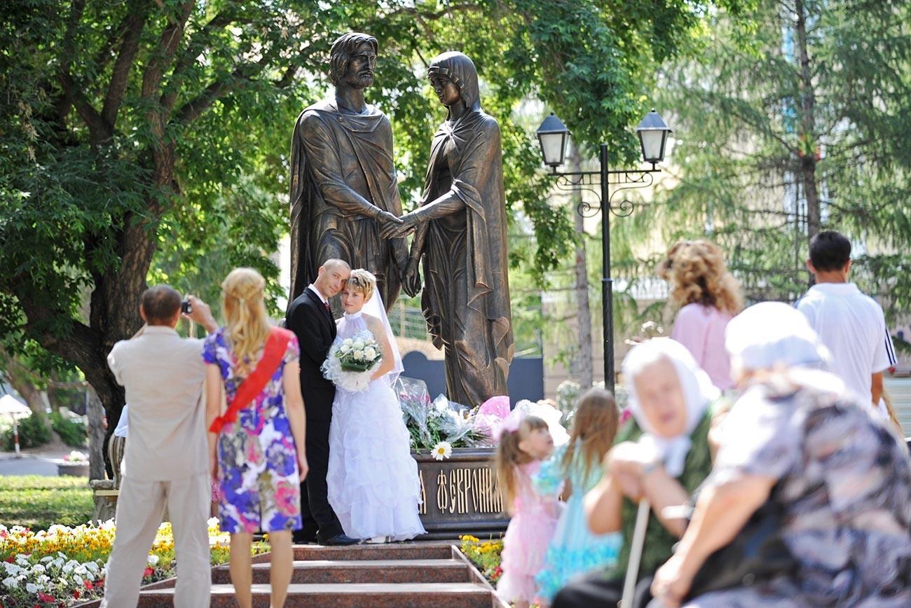 Mladoporočenca se fotografirata pri spomeniku Petra in Fevronije v Omsku.