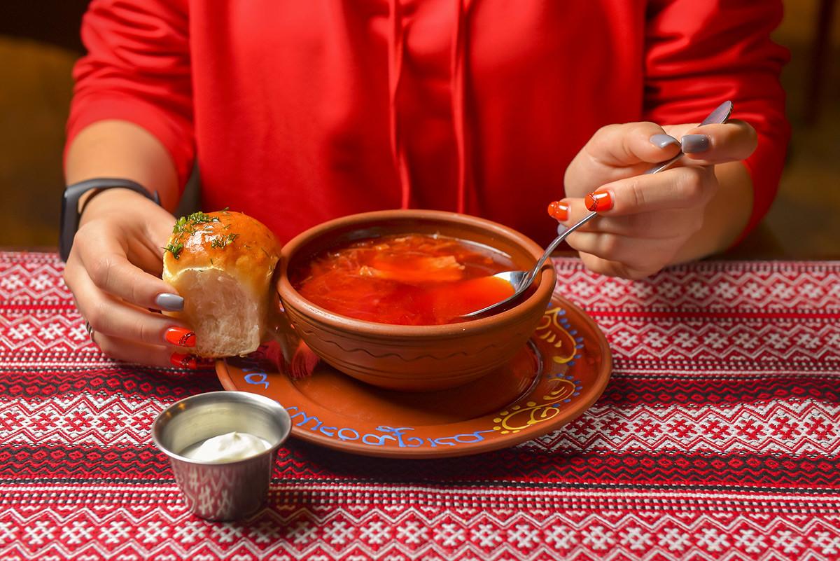 Il borsch servito con panna acida e pane
