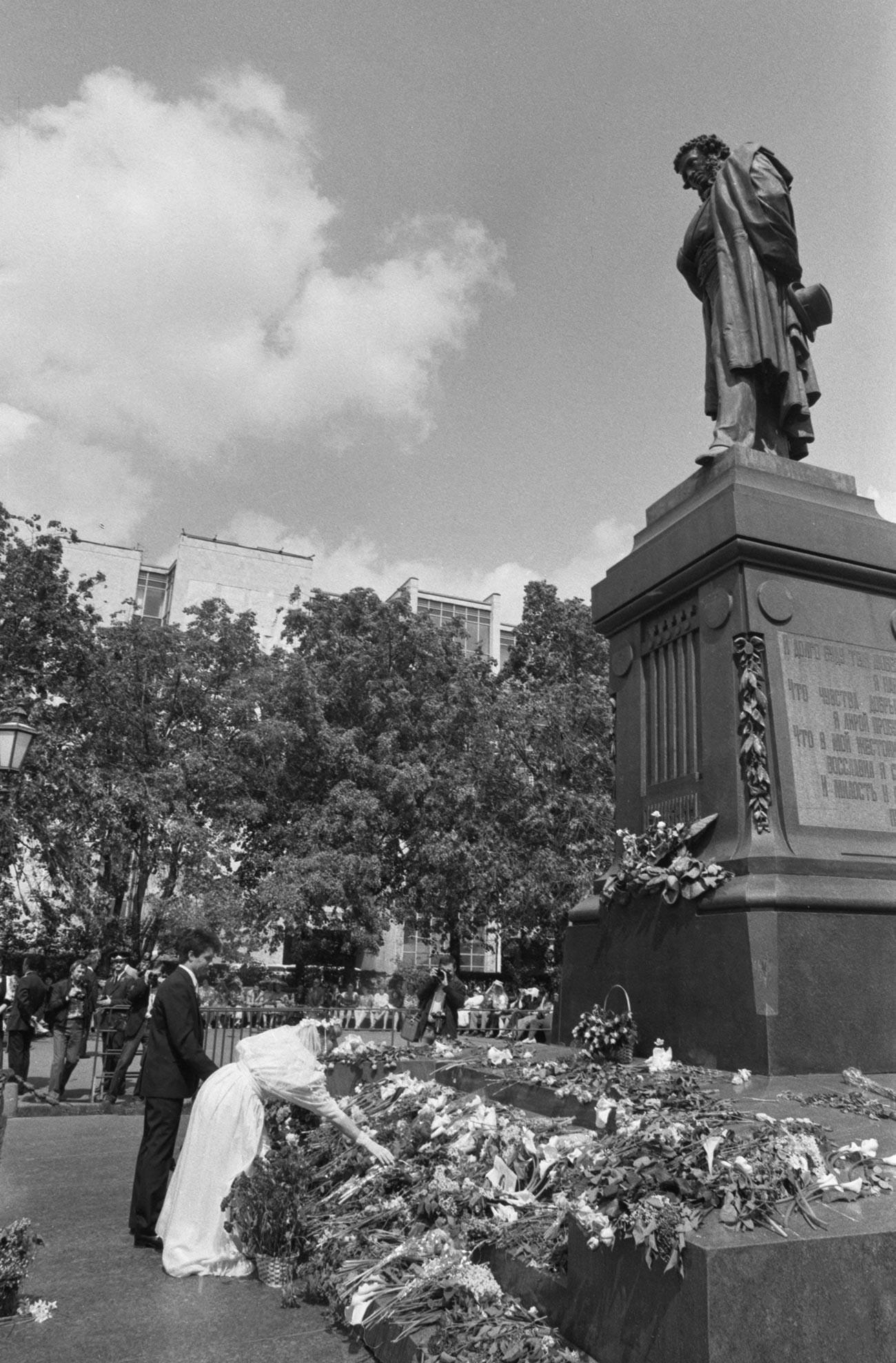Jeunes mariés déposant des fleurs au pied de la statue de Pouchkine, à Moscou