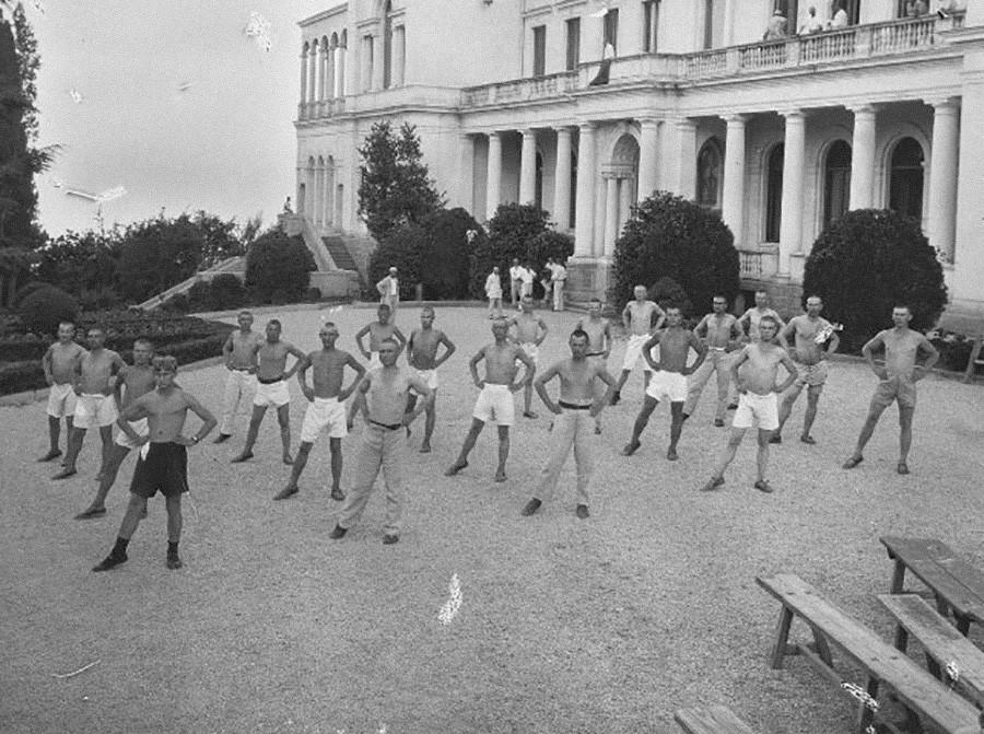 Gruppo di contadini durante una sessione di esercizi mattutini in un sanatorio costruito nell'ex palazzo reale