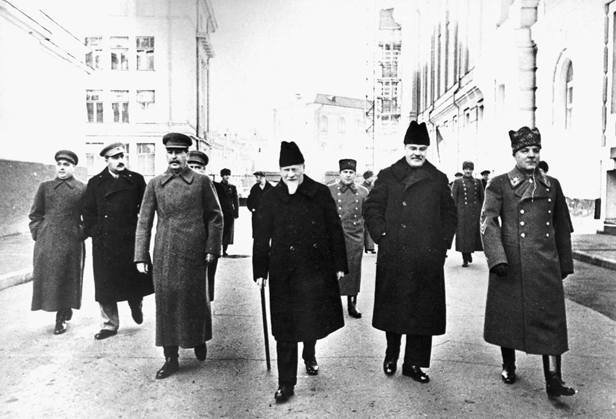 Советските раководители минуваат низ Кремљ пред почетокот на парадата на Црвениот плоштад. Одлево надесно: Георгиј Маленков, Лазар Каганович, Јосиф Сталин, Михаил Калинин, Вјачеслав Молотов и Климент Ворошилов.