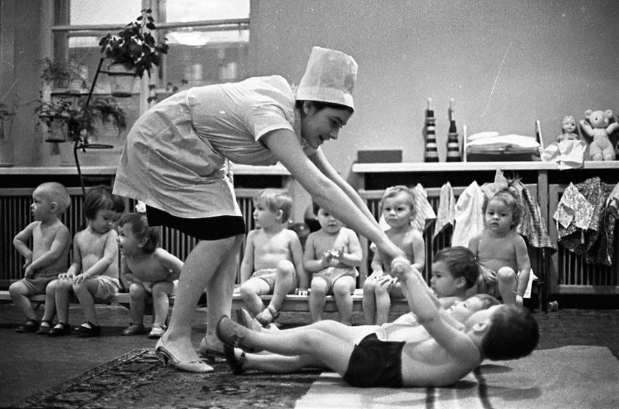 Nella scuola materna si insegnava ai bambini a fare sport regolarmente. Nella foto, una dottoressa mostra ai bambini come fare ginnastica, 1965
