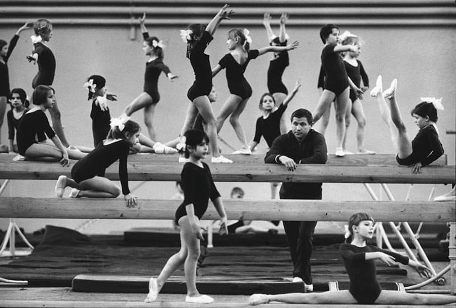 """La ginnastica artistica occupava un posto di rilievo; durante le lezioni di educazione fisica ci si allenava con il cavallo e le parallele; negli anni la Russia ha """"sfornato"""" ginnasti professionisti di altissimo livello. Un gruppo di giovani ginnaste durante un allenamento, 1964"""