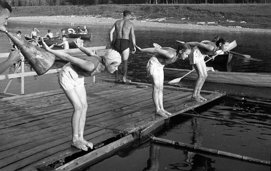 Drei Schulkinder, die sich auf einen Schwimmwettbewerb vorbereiten, 1946