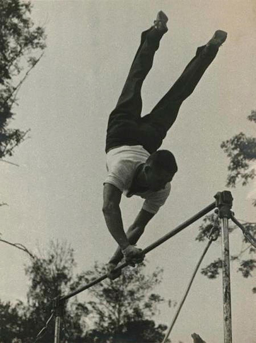 Ein Mann führt einen Trick an einer Reckstange aus, 1935