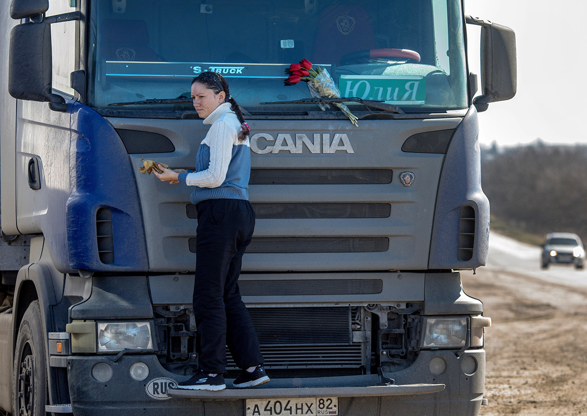 Yulia Lazareva membersihkan kaca truknya.