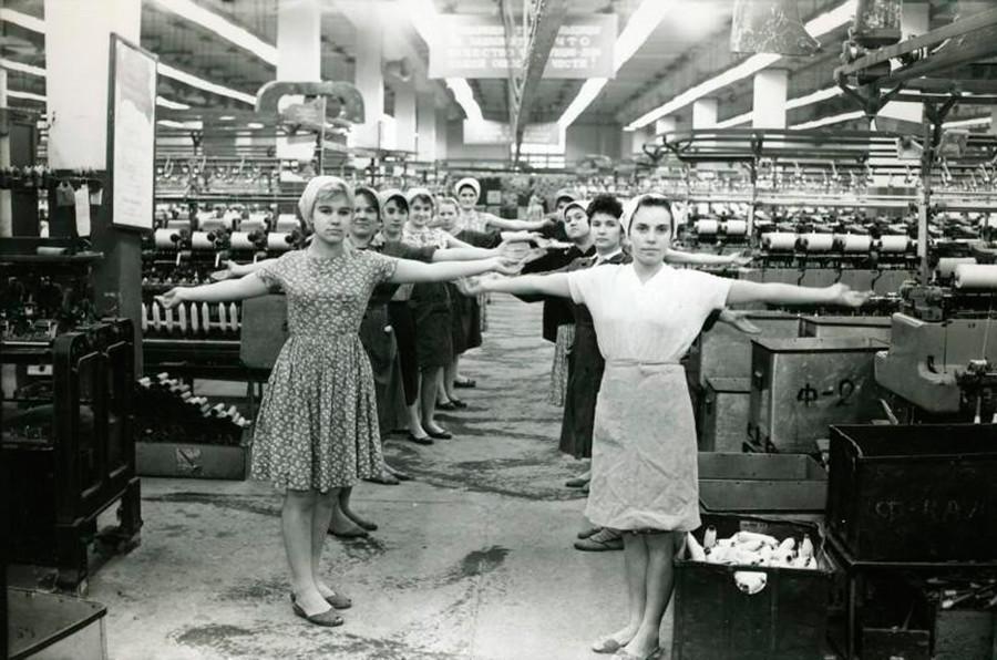 Des ouvriers d'une usine de textile s'étirent avant de prendre leur poste, 1960