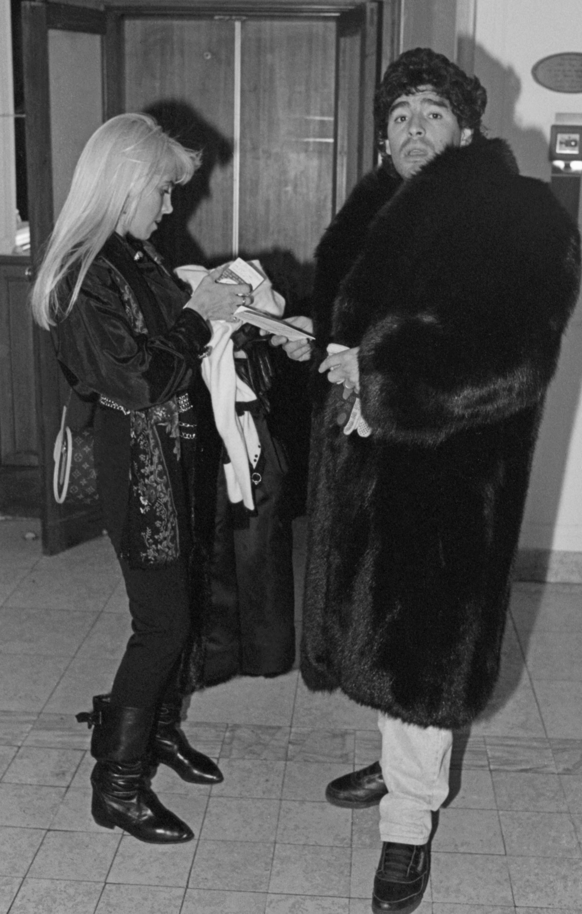 Maradona com casaco de pele no hall do Hotel Berlim, em Moscou, acompanhado da mulher Claudia Villafañe