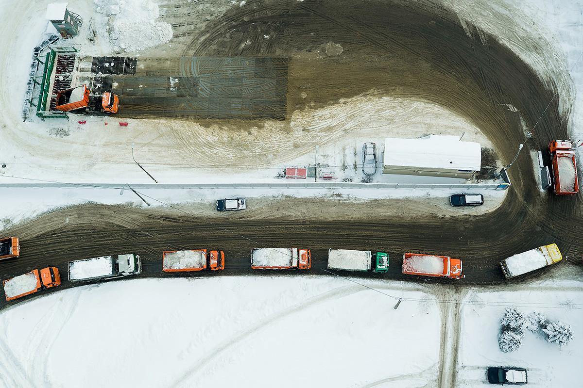Camion in fila verso il punto di scioglimento della neve a Mosca