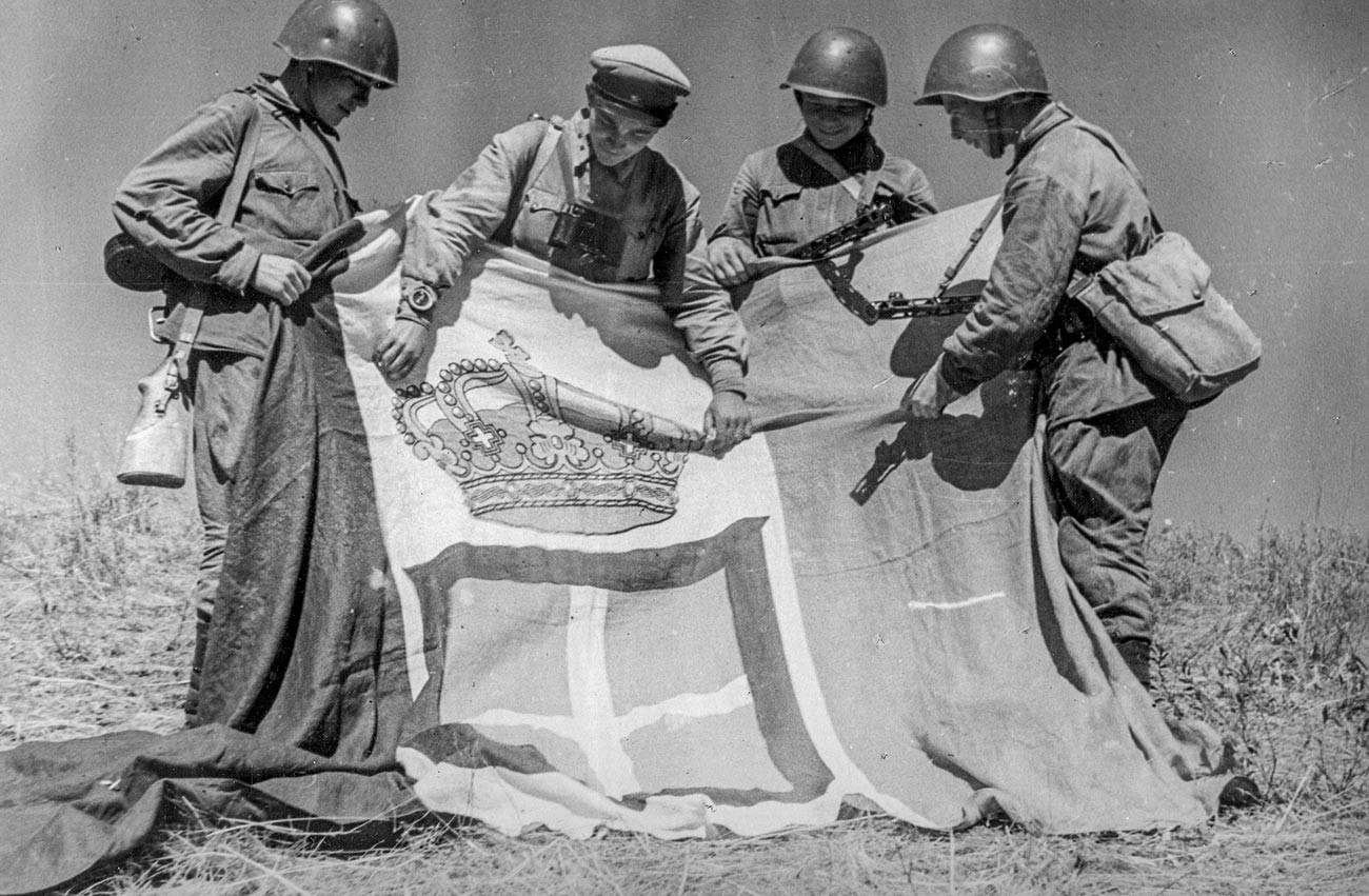 Soviet troops with the captured standard of an Italian regiment.