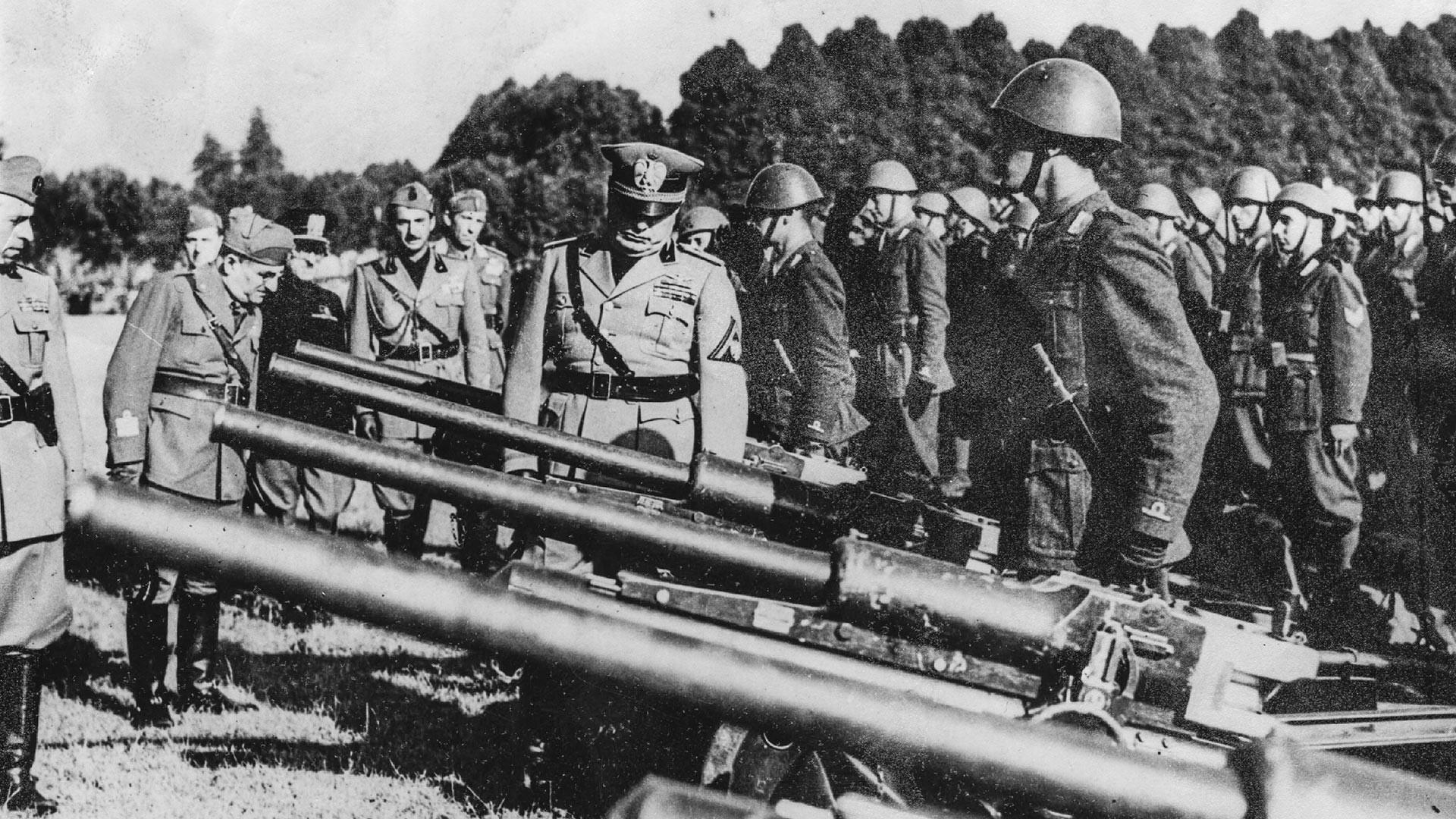 Le dictateur Benito Mussolini inspecte des canons qui seront envoyés sur le front.